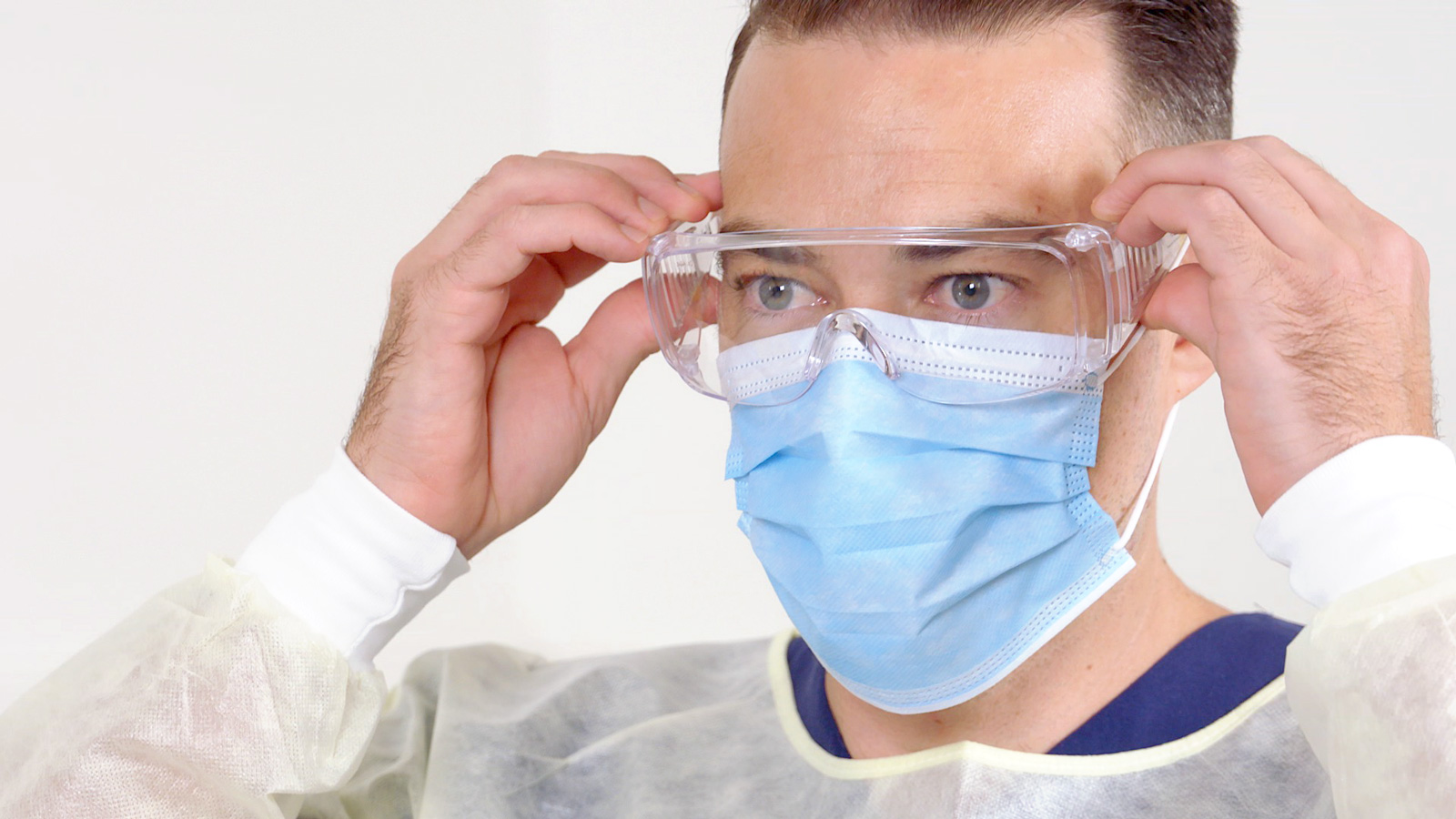 A man in personal protective equipment adjusts his safety glasses