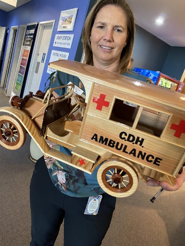 Suzanne Lide holding Ray's handmade gift: a wooden ambulance
